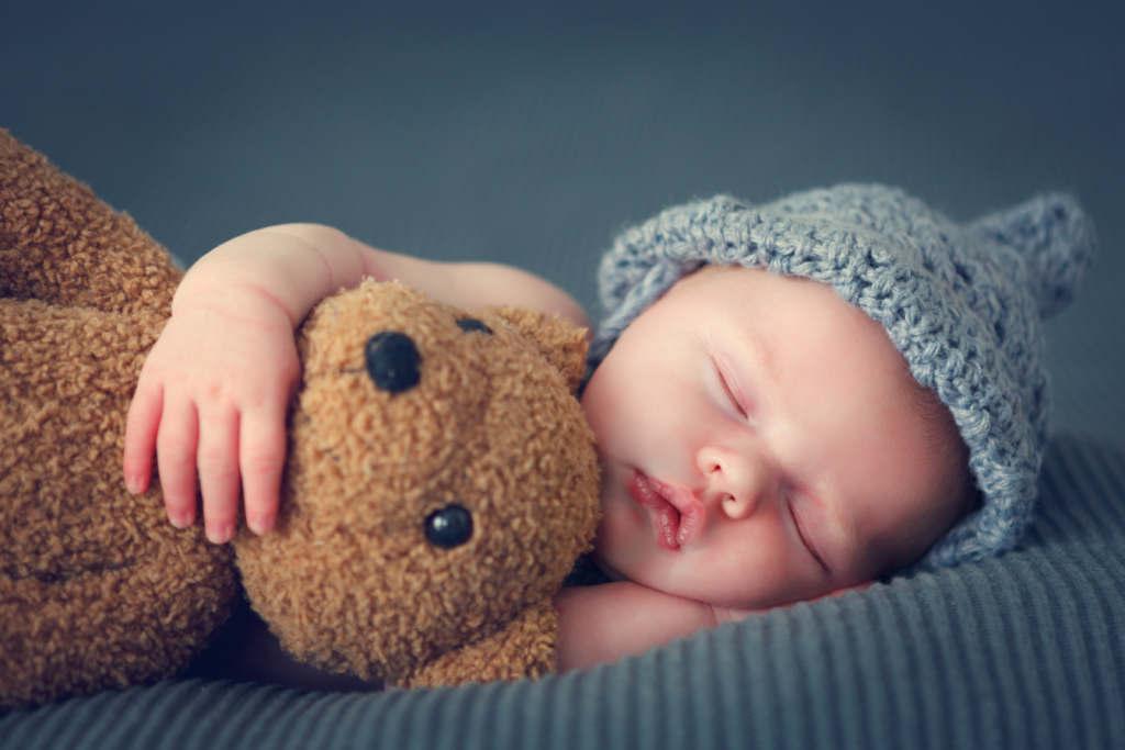 Śpiący w czapce noworodek z misiem
