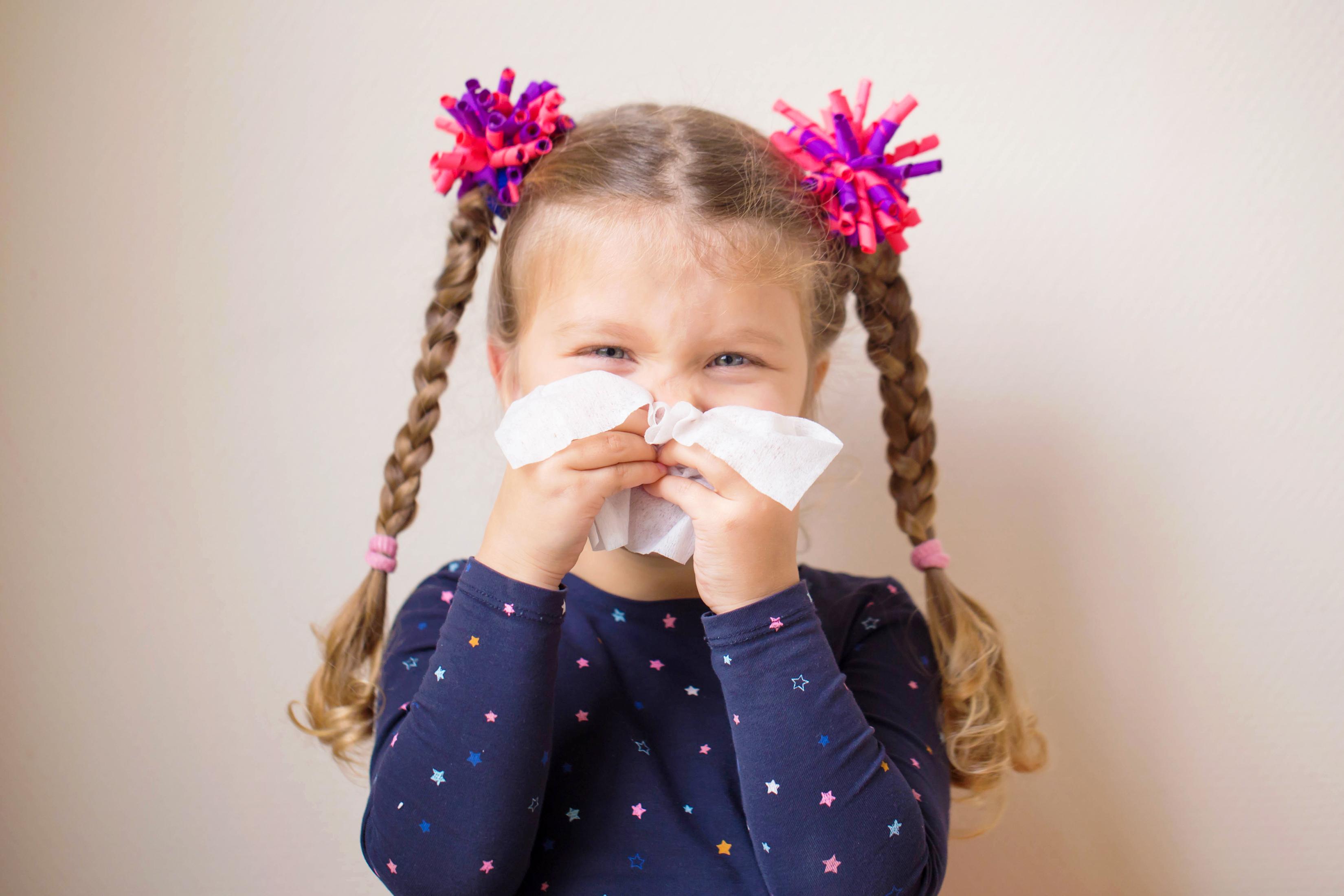Dziewczynka wydmuchująca nos z kataru
